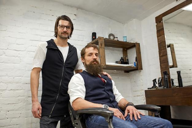 Brutalny facet w nowoczesnym sklepie fryzjerskim. fryzjer sprawia, że fryzura jest mężczyzną z długą brodą. mistrz fryzjer robi fryzurę nożyczkami i grzebieniem