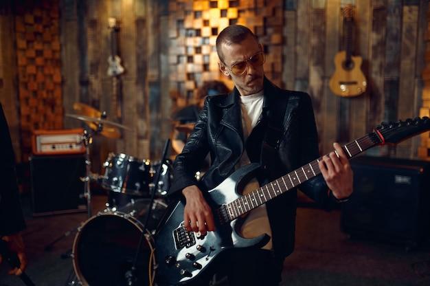 Brutalny gitarzysta z gitarą elektryczną, muzyka występująca na scenie