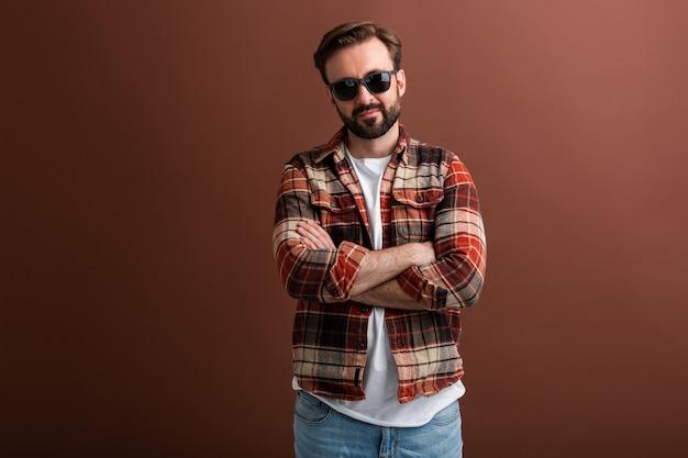 Brutalny hipster przystojny stylowy brodaty mężczyzna na brązowym