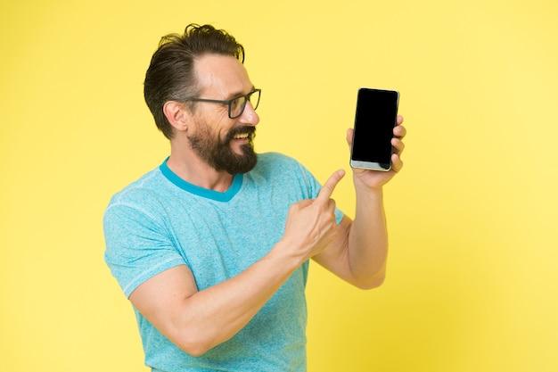 Brutalny kaukaski hipster z wąsami. dojrzały hipster z brodą. brodaty mężczyzna. pielęgnacja męskiego fryzjera. próbuję komuś pomóc. inteligentny człowiek w okularach trzymać smartfona. prezentując produkt. spójrz na to.