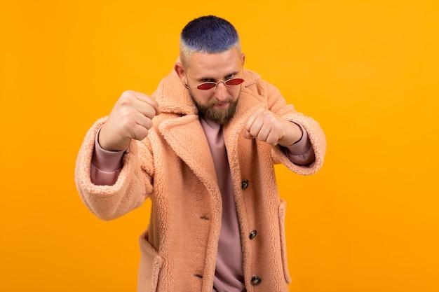 Brutalny kaukaski mężczyzna z krótkimi niebieskimi włosami i czerwonymi okularami w boksie z futrem na pomarańczowo