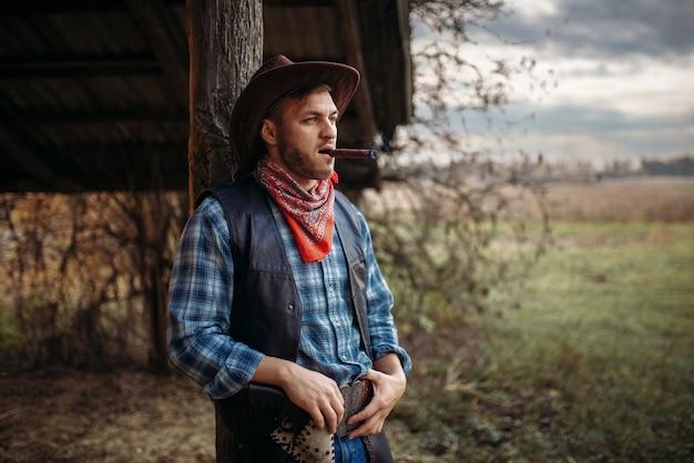 Brutalny kowboj pali cygaro, kultura dzikiego zachodu