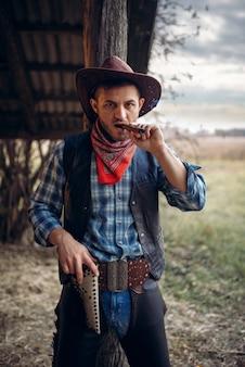 Brutalny kowboj pali cygaro, ranczo w teksasie, western. vintage mężczyzna z pistoletem na farmie, kultura dzikiego zachodu