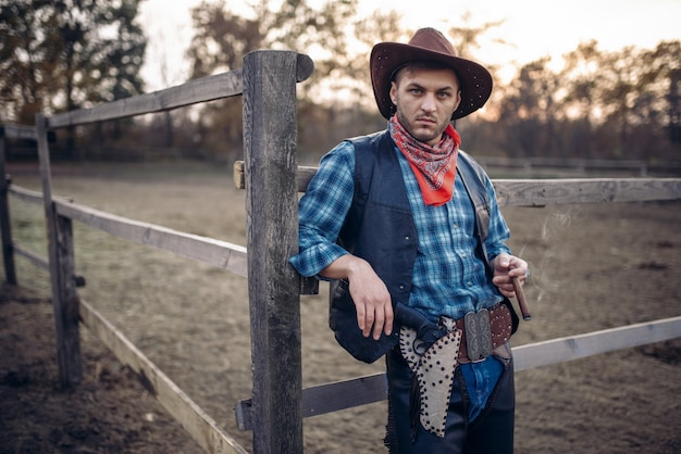 Brutalny kowboj pozuje w zagrodzie dla koni na ranczo