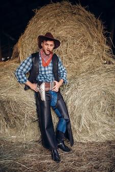 Brutalny kowboj pozuje z cygarem i rewolwerem