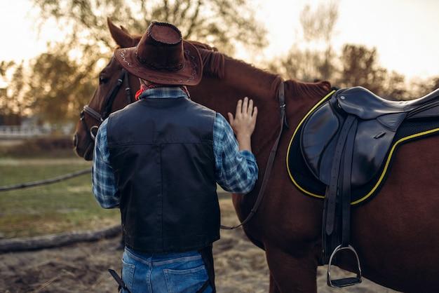 Brutalny kowboj pozuje z koniem, dziki zachód