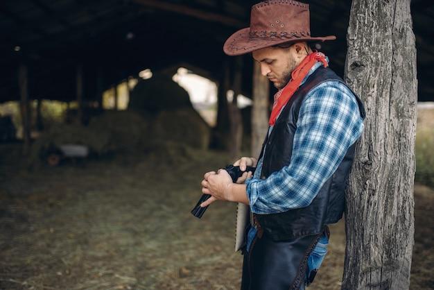 Brutalny kowboj sprawdza swój rewolwer przed strzelaniną