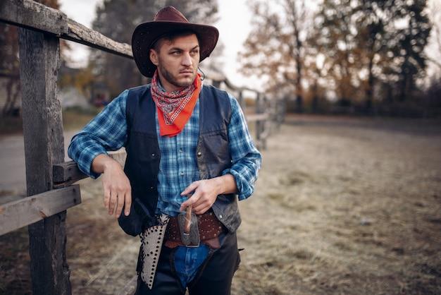 Brutalny kowboj z cygarem w zagrodzie dla koni, ranczo w teksasie, western. vintage mężczyzna z pistoletem na farmie, styl życia na dzikim zachodzie