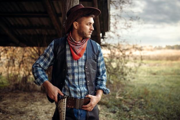 Brutalny kowboj z ręką na rewolwerze, ranczo w teksasie, western. vintage mężczyzna z pistoletem, styl życia na dzikim zachodzie