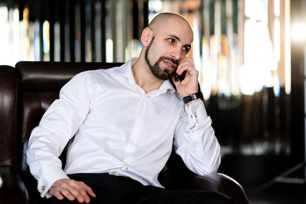 Brutalny łysy mężczyzna rozmawia przez telefon.