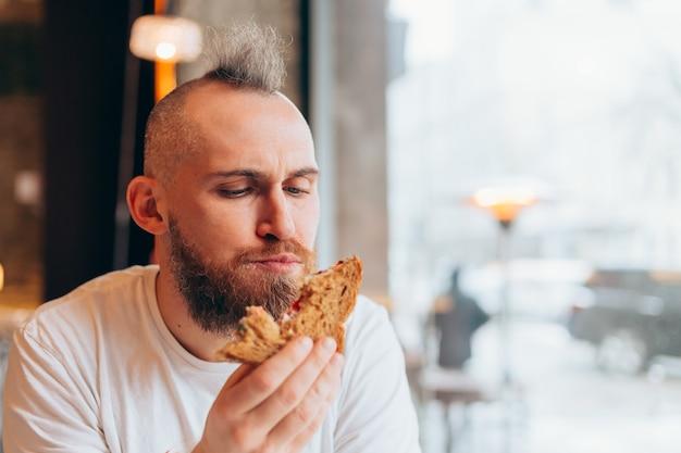 Brutalny mężczyzna o europejskim wyglądzie w kawiarni je pyszną kanapkę