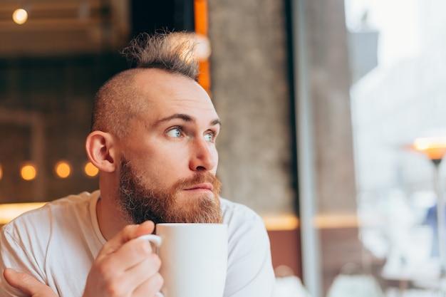 Brutalny mężczyzna o europejskim wyglądzie w kawiarni rano przy filiżance gorącej kawy
