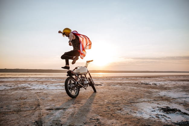 Brutalny mężczyzna skaczący na motocyklu o zachodzie słońca na pustyni