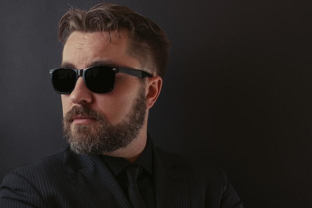 Brutalny mężczyzna w czarnym garniturze i okularach przeciwsłonecznych.