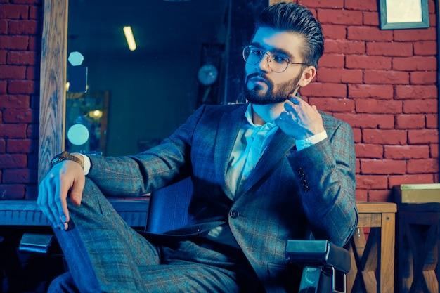 Brutalny mężczyzna w eleganckim garniturze i okularach w zakładzie fryzjerskim