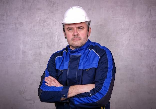 Brutalny mężczyzna w mundurze roboczym i białym hełmie na szarej ścianie