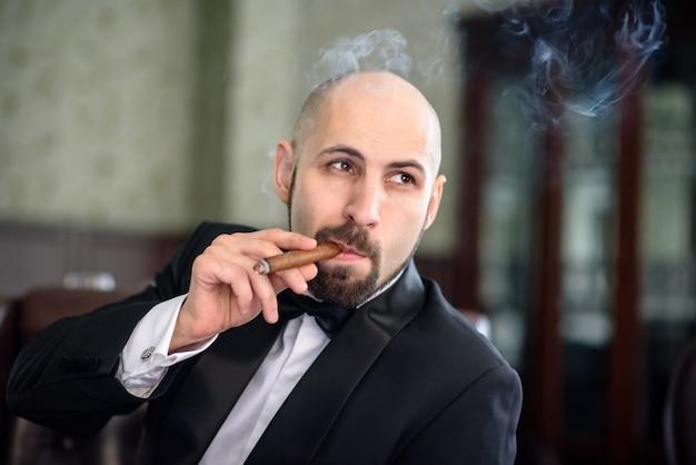 Brutalny mężczyzna w płaszczu pali cygaro