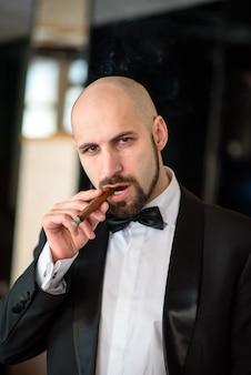 Brutalny mężczyzna w płaszczu pali cygaro.