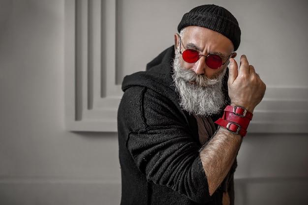 Brutalny mężczyzna w pomieszczeniu w czerwonych okularach. stylowy starzec.