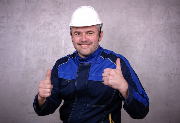 Brutalny mężczyzna w średnim wieku w czarnej kurtce i białym hełmie z uśmiechem na twarzy pokazuje gest dwóch kciuków w górę. szczęśliwy mechanik na szarym tle
