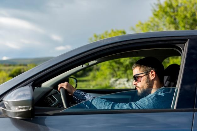 Brutalny mężczyzna z okularami przeciwsłonecznymi jedzie samochód