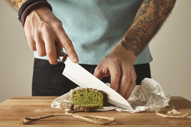 Brutalny mężczyzna z wytatuowanymi rękami kroi zdrowy szpinak domowy zielony rustykalny chleb z rocznika nożem na plasterkach. stół drewniany z białej płyty
