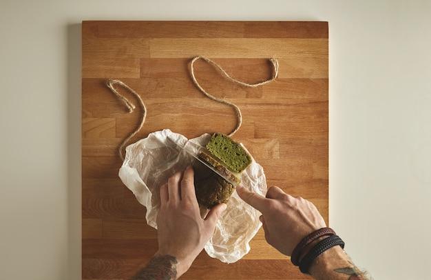 Brutalny mężczyzna z wytatuowanymi rękami kroi zdrowy szpinak domowy zielony rustykalny chleb z rocznika nożem na plasterkach. widok z góry na biały deska drewniana