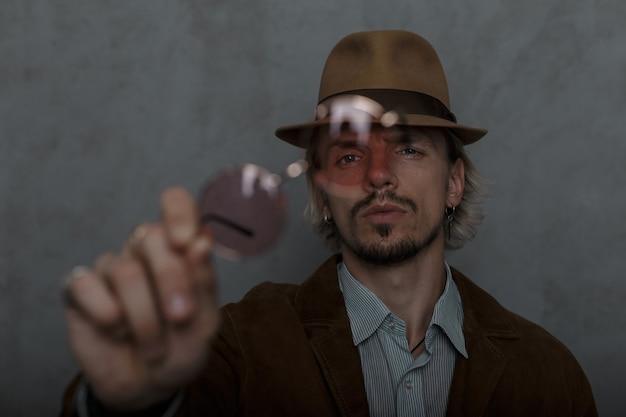 Brutalny młody człowiek w kapeluszu vintage w ubraniach w stylu retro stoi i pokazuje w aparacie czerwone okrągłe okulary vintage. atrakcyjny model facet pozowanie w pokoju. skoncentruj się na okularach. zbliżenie.