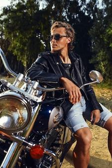 Brutalny Młody Mężczyzna W Okularach Przeciwsłonecznych, Niebieskich Dżinsach I Czarnej Skórzanej Kurtce Siedzący Na Niestandardowym Motocyklu Na świeżym Powietrzu Premium Zdjęcia