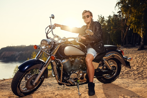 Brutalny młody mężczyzna w okularach przeciwsłonecznych, niebieskich dżinsach i czarnej skórzanej kurtce, siedzący na zewnątrz na niestandardowym motocyklu