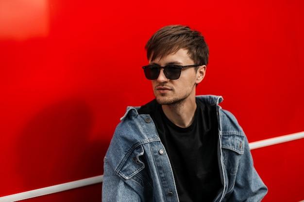 Brutalny modny młody hipster mężczyzna w modnej niebieskiej dżinsowej kurtce w stylowych okularach przeciwsłonecznych z brodą w pobliżu czerwonej metalowej ściany na ulicy. atrakcyjny model facet odpoczywa w letni dzień w mieście.