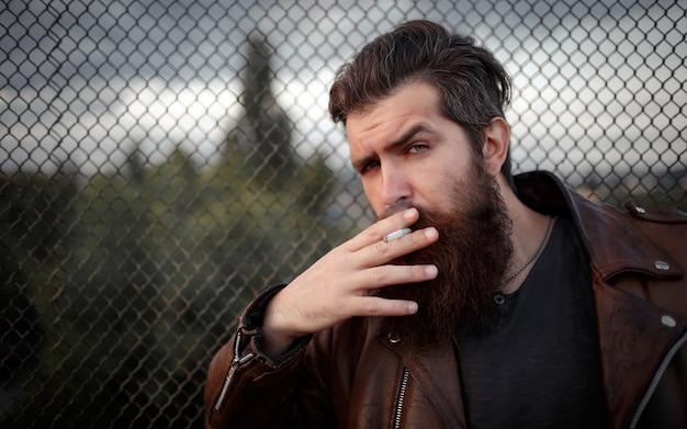Brutalny motocyklista z długą brodą, wąsami i siwymi włosami w brązowej skórzanej kurtce pali papierosa