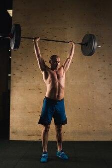 Brutalny, muskularny mężczyzna z pociągiem brody ze sztangą podniesioną nad głową w siłowni