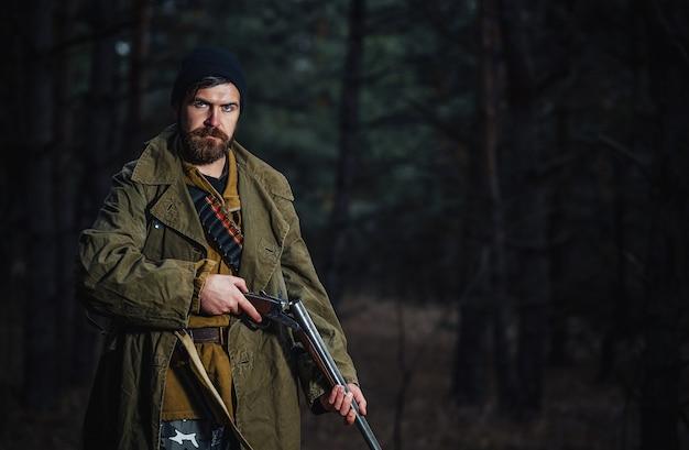 Brutalny myśliwy brodaty mężczyzna w ciemnym kapeluszu i kurtce khaki w długim płaszczu trzyma rozładowaną broń na tle ciemnego lasu