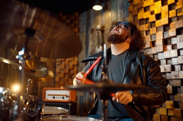 Brutalny perkusista za zestawem perkusyjnym na scenie