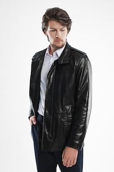 Brutalny przystojny nieogolony mężczyzna z brodą i wąsami w skórzanej kurtce