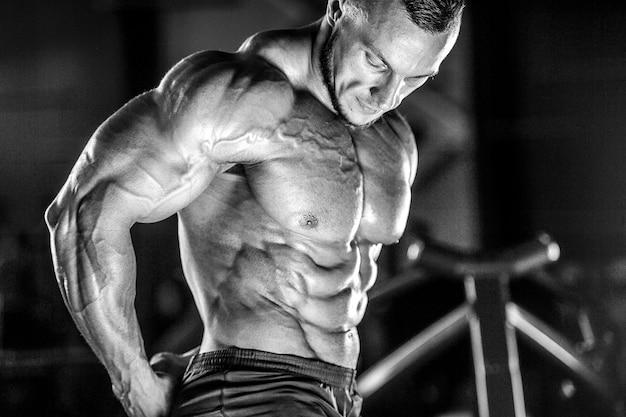 Brutalny silny atletyczny mężczyzna mięśni trening kulturystyka kulturysta mięśni robi ćwiczenia w siłowni