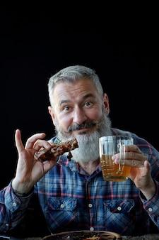 Brutalny siwy dorosły mężczyzna oszalały na punkcie steku i piwa z musztardy, wakacji, festiwalu, oktoberfest lub dnia świętego patryka
