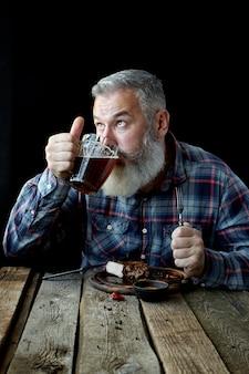 Brutalny siwy dorosły mężczyzna szalony na musztardowym steku i piwie, festiwal, oktoberfest lub dzień świętego patryka