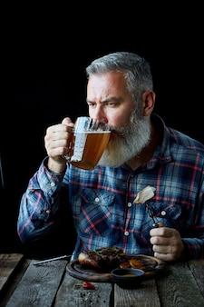 Brutalny siwy dorosły mężczyzna z brodą zjada stek musztardowy i pije piwo, wakacje, festiwal, oktoberfest lub dzień świętego patryka