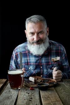 Brutalny siwy dorosły mężczyzna z brodą zjada stek musztardowy i pije piwo