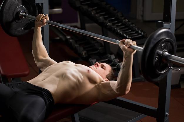 Brutalny wysportowany mężczyzna pompowania mięśni w wyciskaniu na ławce