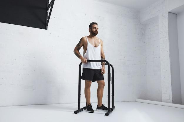 Brutalny, wytatuowany, brodaty męski sportowiec w pustej białej koszulce ze zbiornikiem, stojący obok równoległych drążków i drążka, patrząc z boku, gotowy do treningu, patrząc z boku