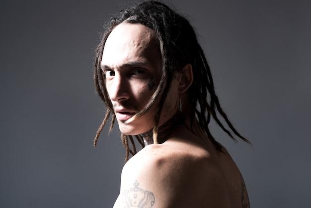 Brutalny wytatuowany mężczyzna tatuaż moda brutalny portret faceta