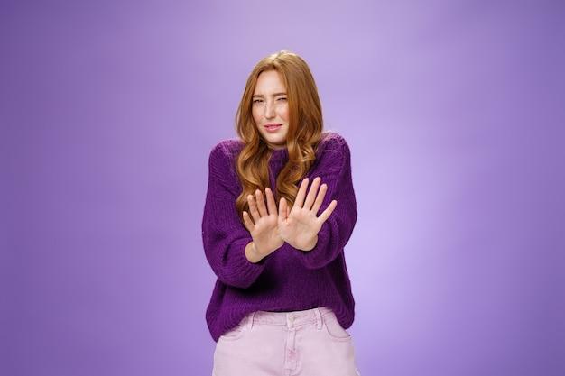 Brutto to zabrać. portret zniesmaczonej rudej kobiety cofa się i macha dłońmi nad ciałem w odmowie i bez żadnego gestu, krzywiąc się i mrużąc oczy z powodu nieprzyjemnego zapachu lub niechęci nad fioletową ścianą.