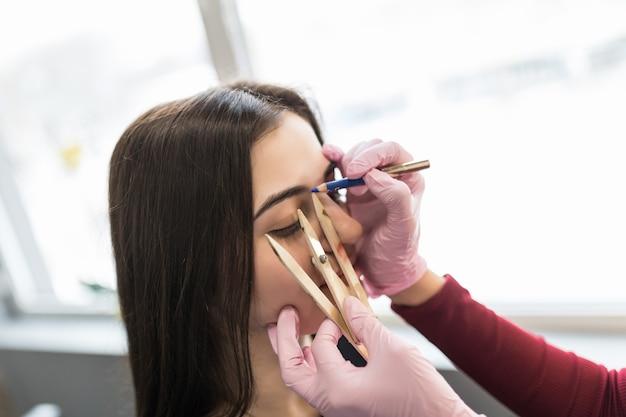 Brwi microblading pracują w salonie kosmetycznym