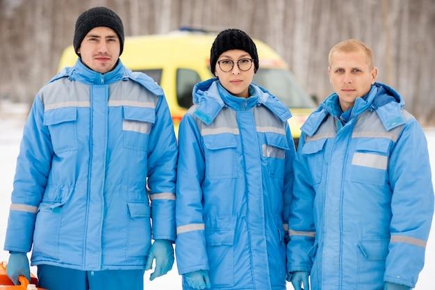 Brygada trzech młodych ratowników medycznych w niebieskiej zimowej odzieży roboczej i stojących rękawiczkach