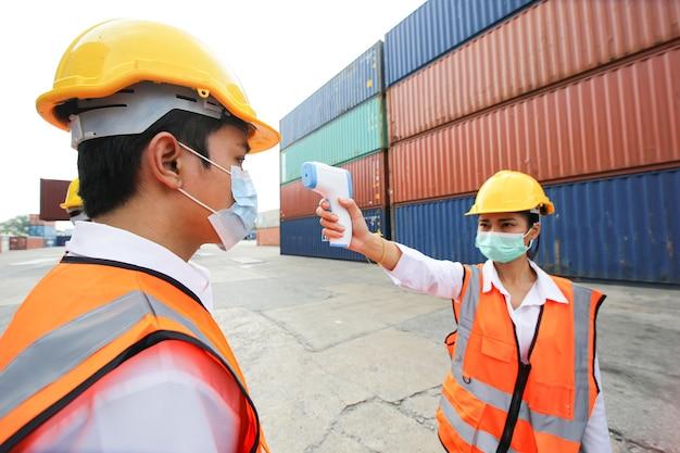 Brygadzista kontroluje załadunek kontenerów ze statku towarowego cargo do importu i eksportu. pracownik magazynu kontenerowego.