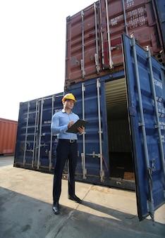 Brygadzista kontroluje załadunek kontenerów ze statku towarowego cargo do importu i eksportu.