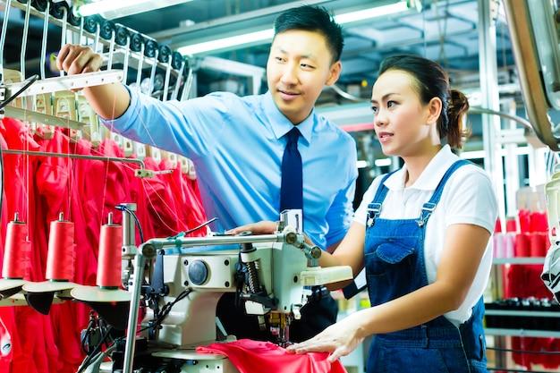 Brygadzista w fabryce coś wyjaśnia